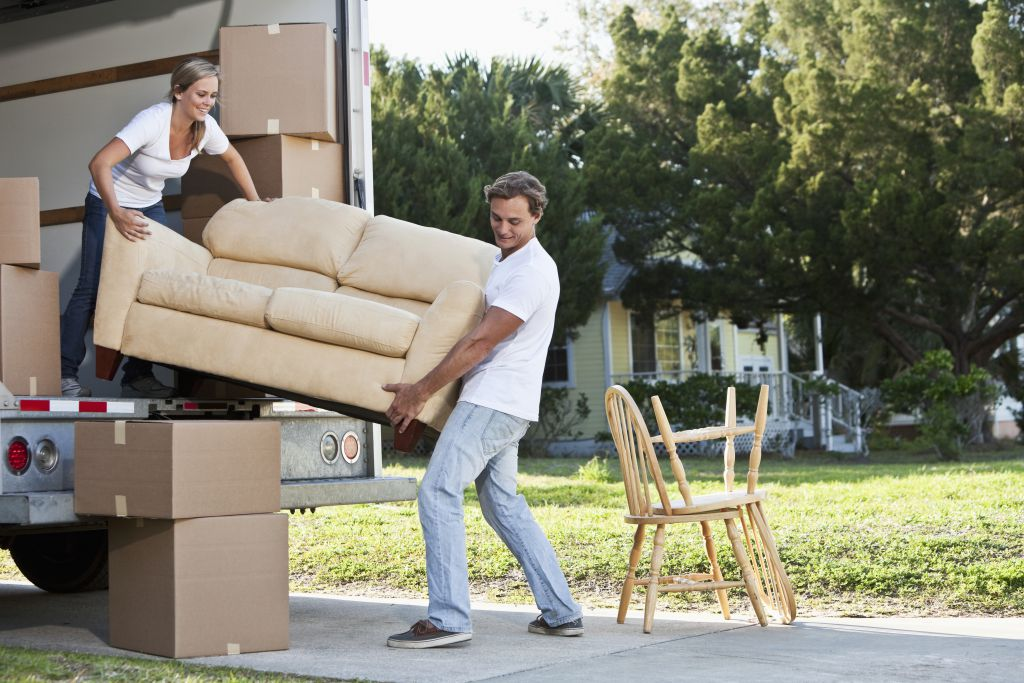 man and woman carrying sofa out of removal van