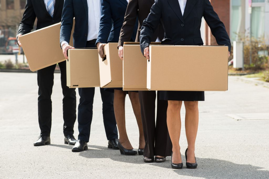 people in office wear carrying boxes