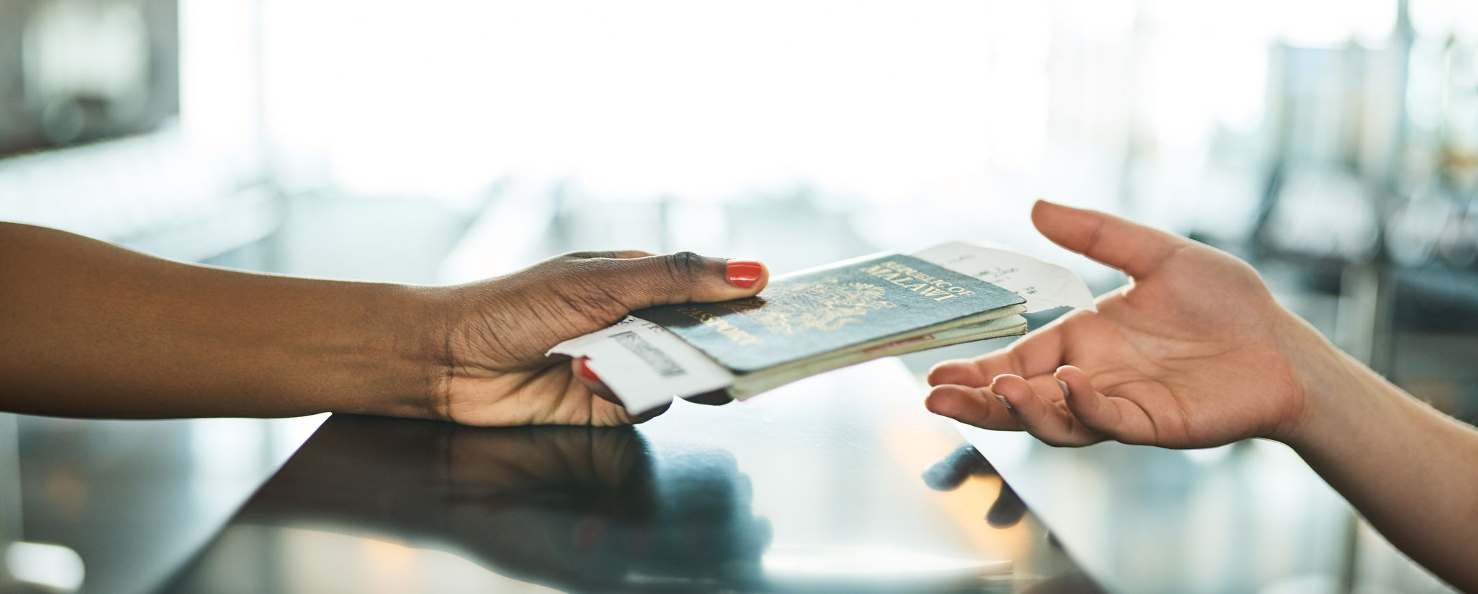 Cropped shot of an unrecognizable woman handing over her ID book at a boarding gate in an airport